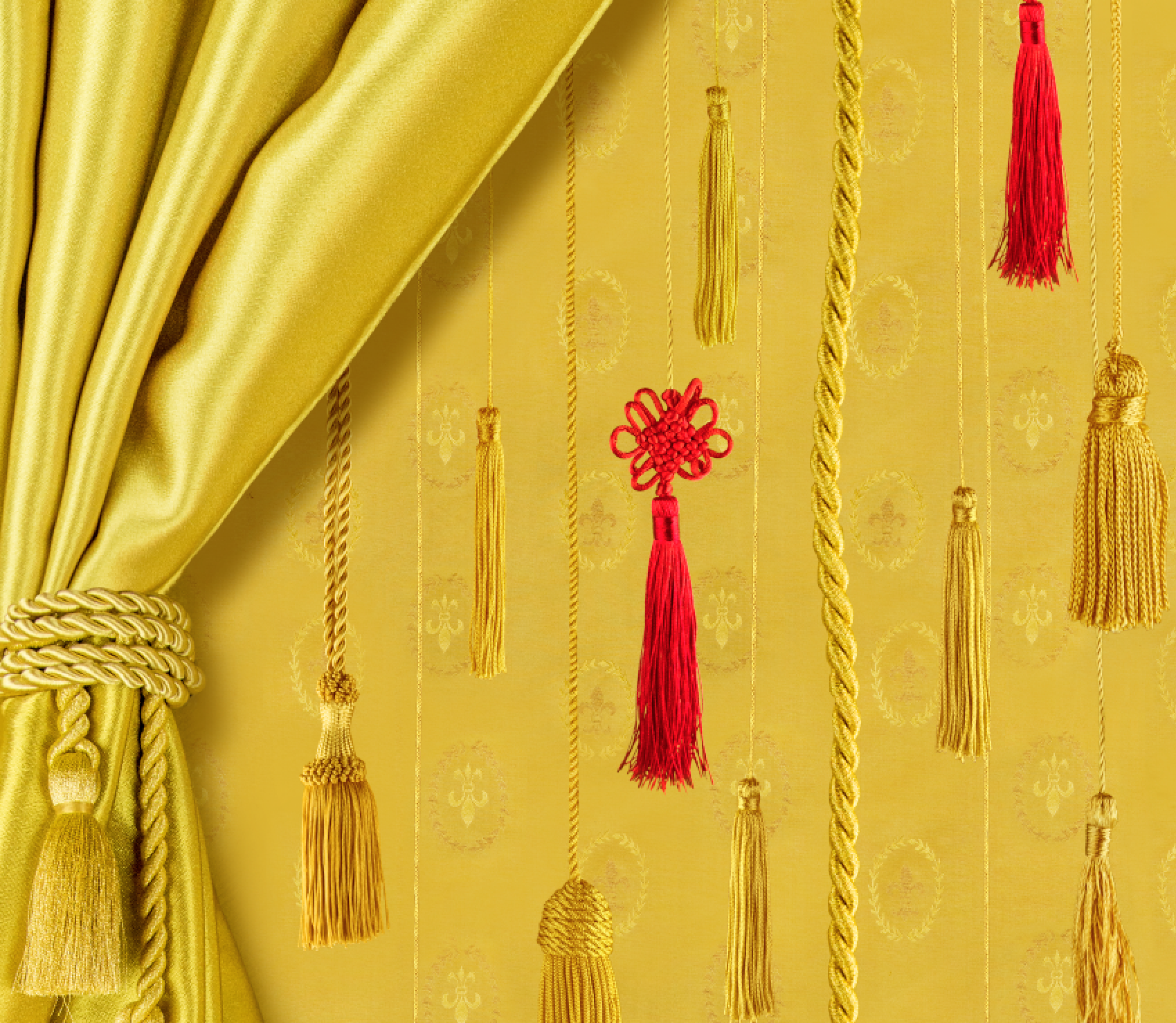 A yellow curtain is pulled to the side by a shiny, gold rope. It reveals eight gold Chinese endless knots and two red Chinese endless knots, which are made from the same rope that is holding the curtain to the side. They are suspended at varying depths and heights.