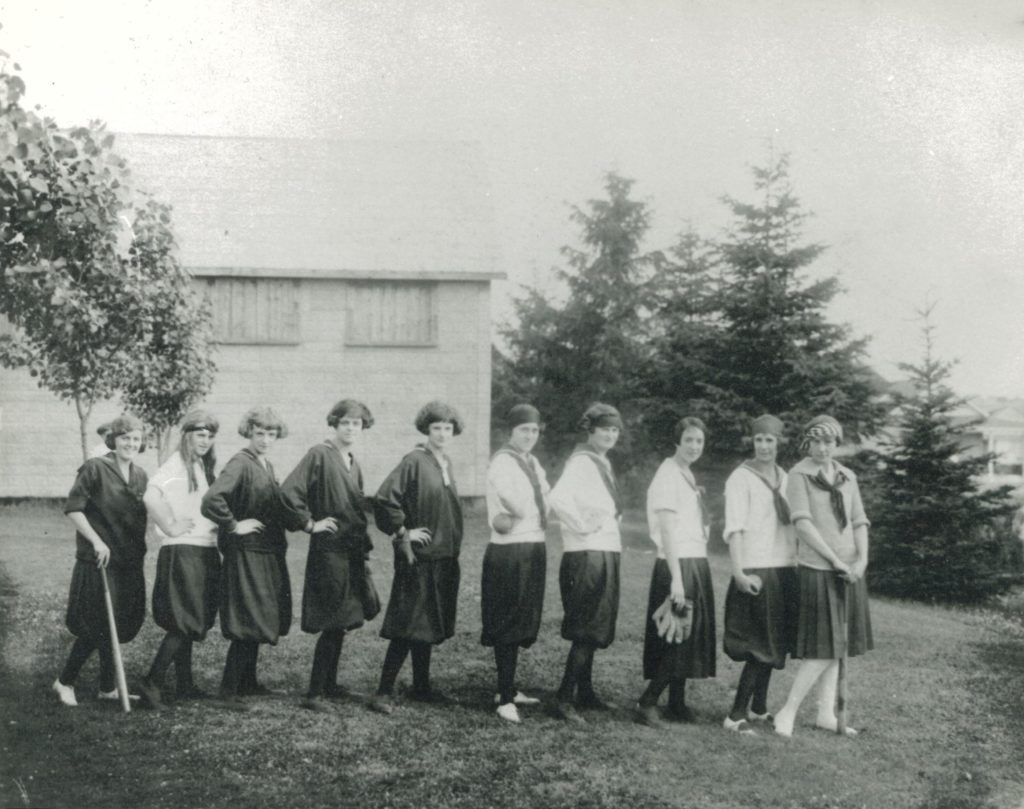 A lineup of young women pose in their softball uniforms. Some of the women have softball batt or mitt in their hands. Behind them is a wooden house and tall pine trees.