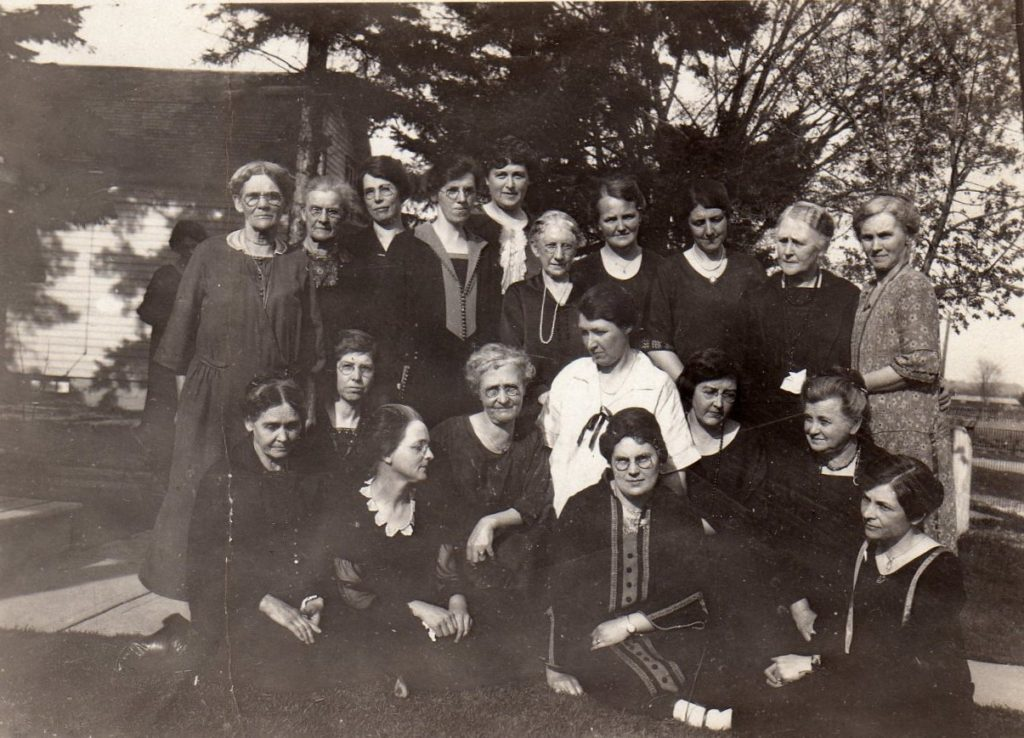 Two rows of older women pose for a photo. Behind them is a building and some trees. The first row of women sit on the ground and the second row stand. They are all wearing ankle length dresses with long sleeves. Some of the women are facing each other as if in conversation, while others face the camera.