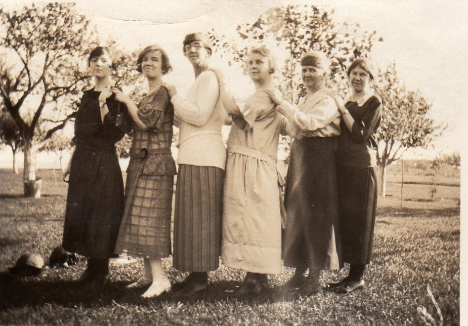 Six young and older women line up and pose in a field with trees behind them. The women wear dresses and skirts that reach their ankles. They have their hands on each other's shoulders and they tilt their heads to face the camera.