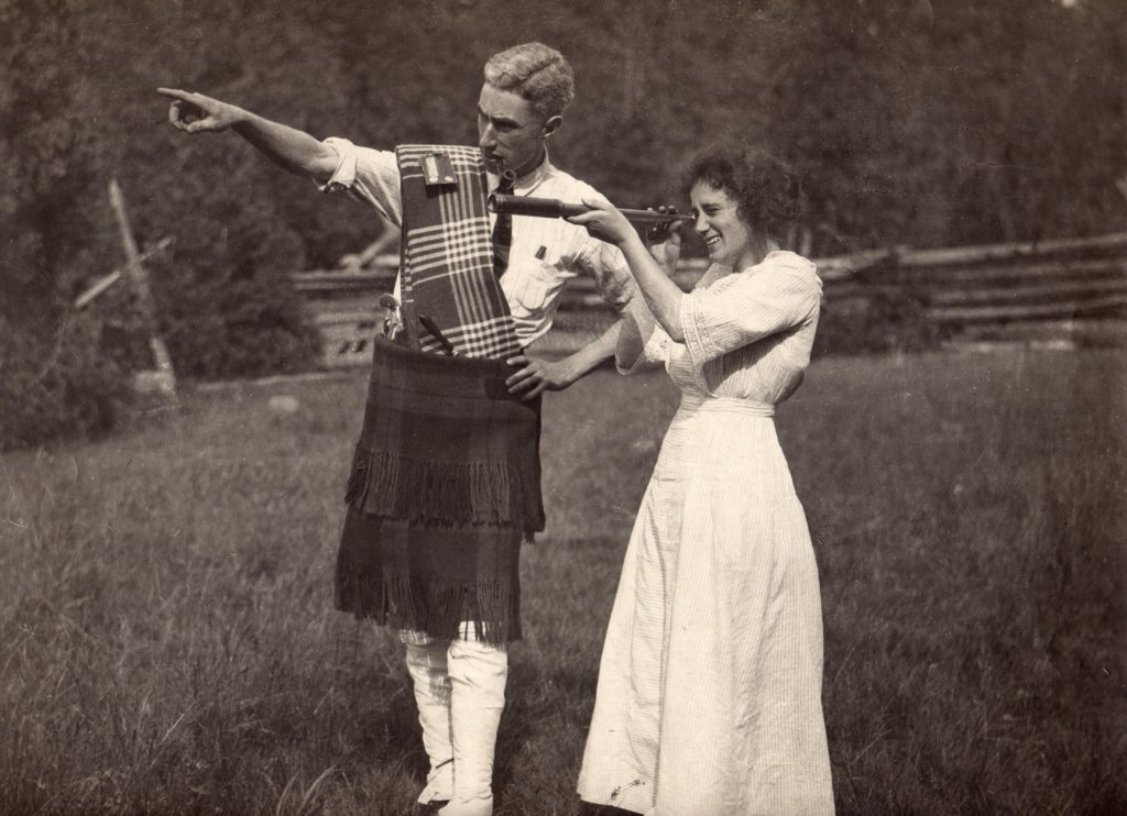 A man and a woman stand in a field with a wooden fence and thick trees in the background. The two stand beside each other as the woman peers into a telescope. The young ma is dressed in a two layered plaid skirt, high socks, and a plaid scarf that is diagonal along his chest. He leans close to the woman and points towards the left of the image. The woman is wearing a long dress with sleeves to her elbows and she holds the telescope to her eye.