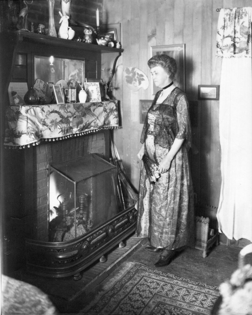 A woman in a formal ankle length dress stands inside a home, looking down at the brick fireplace. A fire is lit and above is a two shelf mantel with picture frames and knick-knacks.  The wall behind the woman is wooden wall with three picture frames and window curtains. The floor is wooden and the corner of a patterned carpet can  be seen.