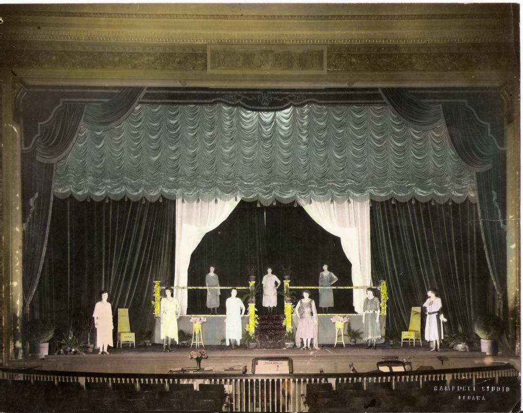 The image is a wide shot of the theatre stage. We can see the first few rows of the seats. On the stage, large curtains drape and frame the nine actresses on stage. The women are dressed in formal dresses or skirts that reach their ankles. They are spaced out on the stage; six are on the main floor and three are on a platform that's about two feet off the floor. Spaced out on the main floor of the stage are pots and vases full of plats, shrubs, and flowers.