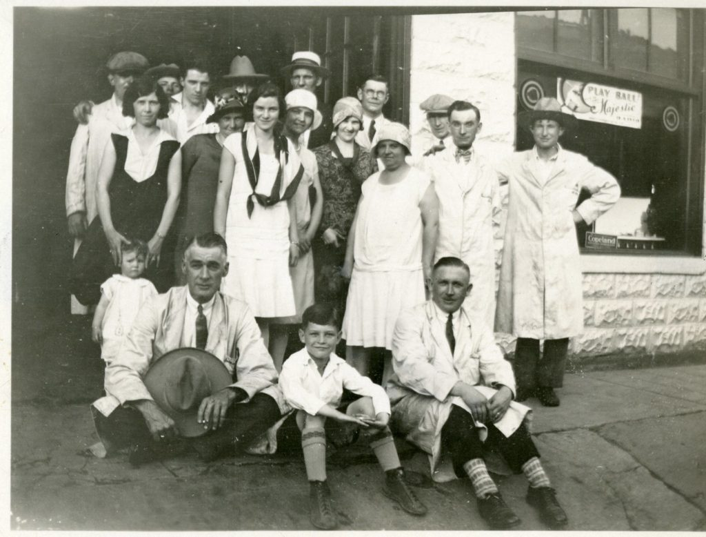 A group of men, women, and children pose for a photo on the sidewalk outside a building. Most of the men are wearing long coats with either a tie or bowtie. The women wear dresses that reach their knees. There are two children in the image; a young boy sits on the ground in between two men, and the other is a toddler, standing yet being held by a young woman.