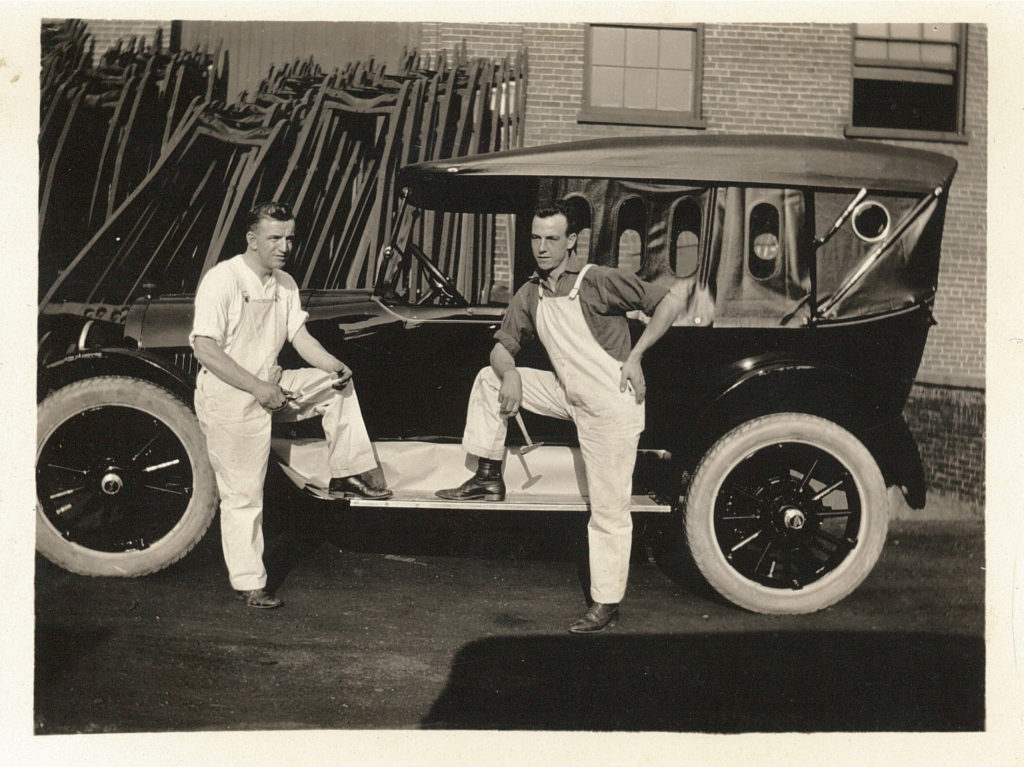 Two men stand with one foot on the ledge of a car. The men are wearing overalls and have tools in their hands.