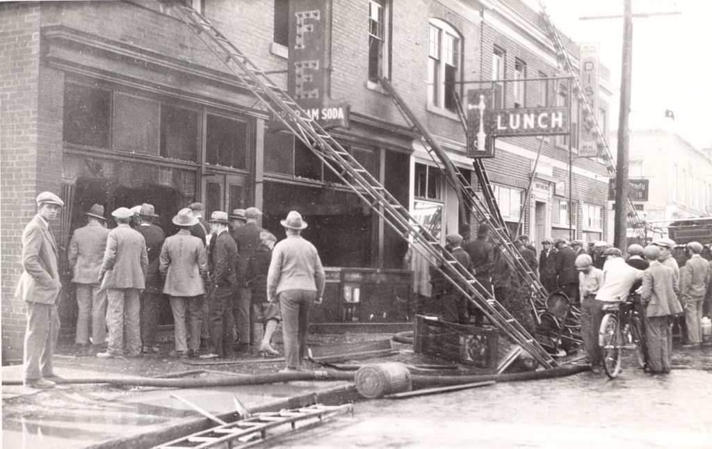 """Two groups of people gather around a damaged two-story building. A sign with the word, """"Lunch"""" hangs on the side of the building. Ladders stretch up to the second floor windows of the building. Hoses and debris lay in the street."""
