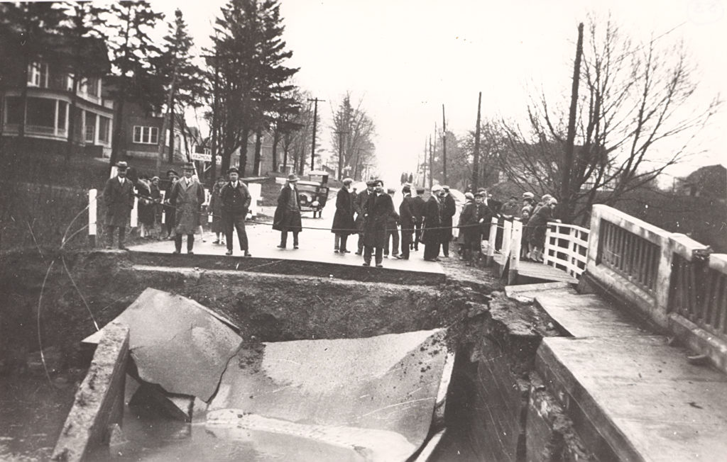 Set in townhouse lined street, group of people stretches across the edge of a collapsed bridge. The debris lies in the foreground and the area is roped off from the group.