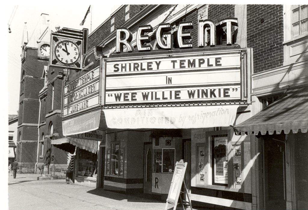 """The front of the theatre is a part of a brick building lined street. In front, is the ticket booth, which has posters and signs lined up along the wall. The marquee above the theatre entrances reads, """"Shirley Temple in 'Wee Willie Winkie'"""". Above the marquee, the word, """"Regent"""" is written in capital letters and with lights. Below the marquee is a cloth sign reads, """"Air Conditioned by Refridgeration""""."""