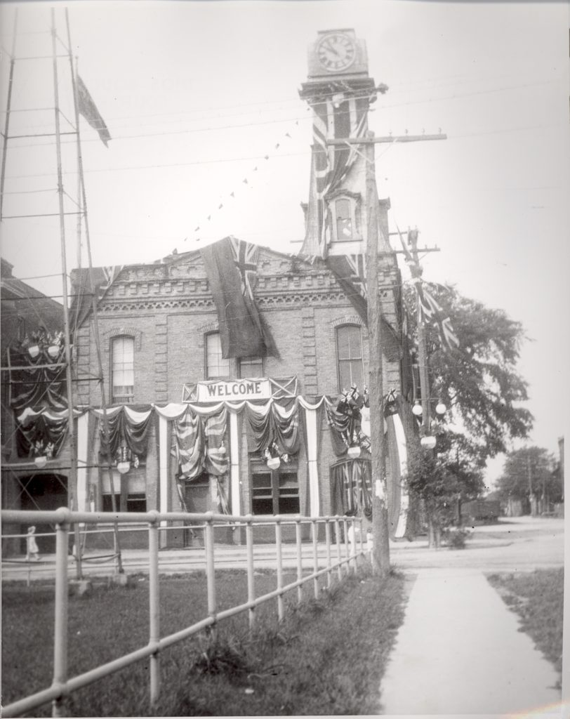 """Across a short sidewalk, the side view of a two-story building with a clock tower is draped in bunting and flags. Underneath a second-story window, a sign reads, """"Welcome""""."""