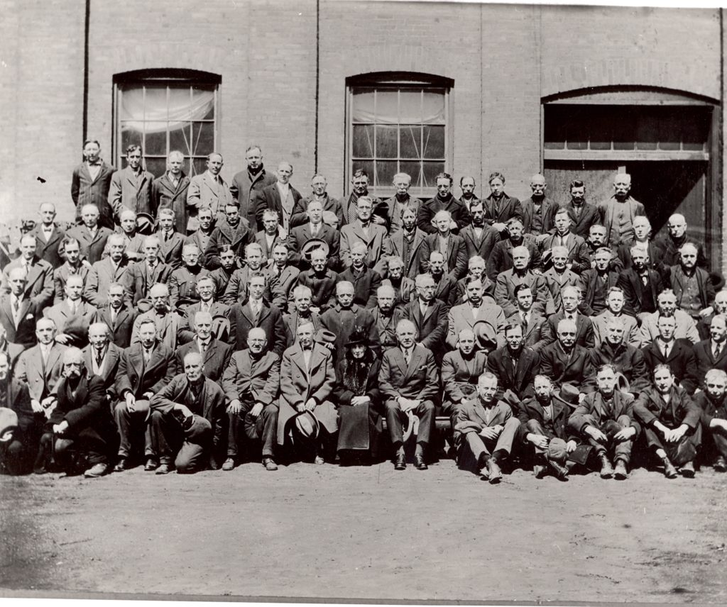 This large group portrait features men in 5 rows. They are all dressed in suits. Behind them is the factory building.