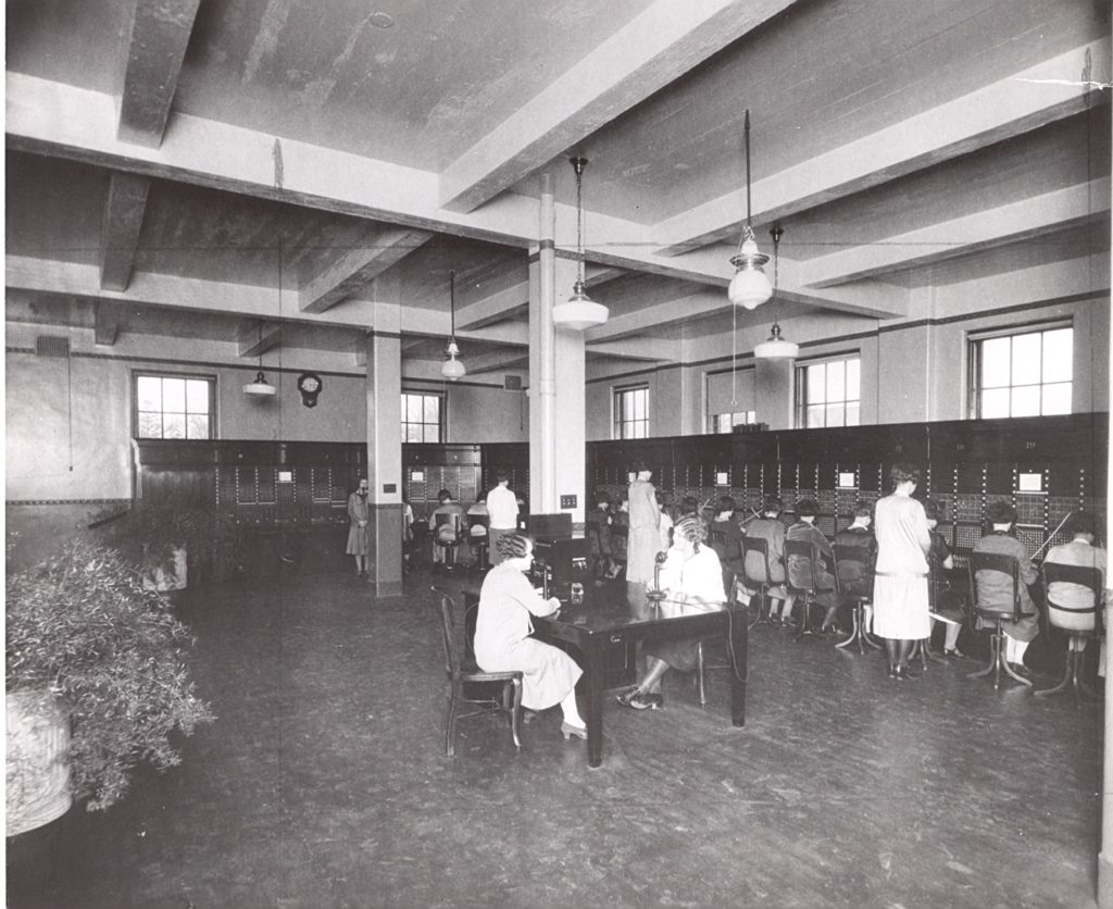 In a large room with tall ceiling, women sit along the walls of the room, facing the switchboards on the walls. In the middle of the room, two women sit a table and appear to be using a two-piece phone.