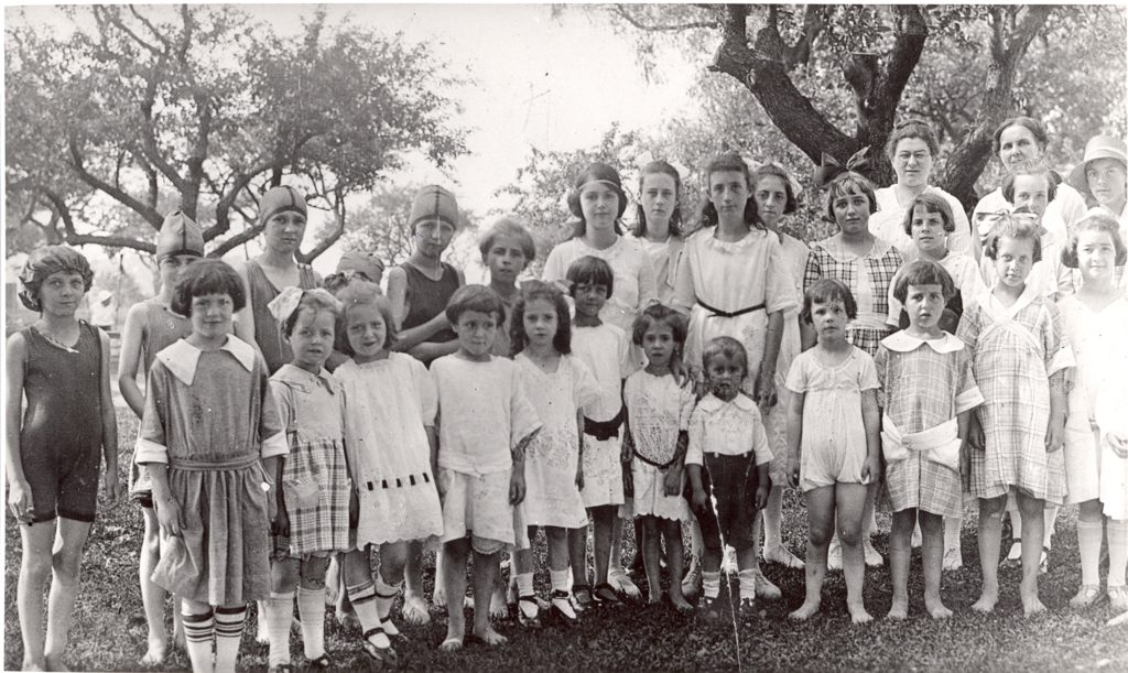 A mix of children, from toddlers to teenagers, pose for the photo. Some are dressed in swimsuits, dresses, or a pants and collared shirts.