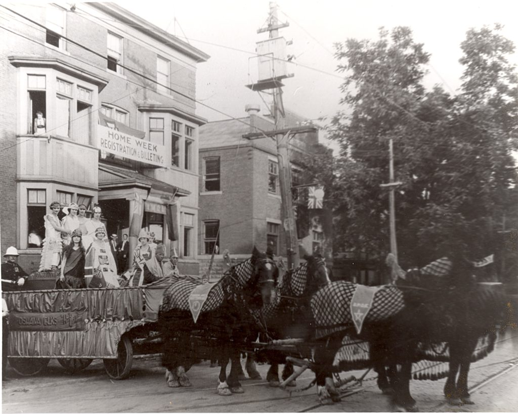 """A float full of well dressed people is carried by four black horses. On the side of the of the float, a sign reads, """"Oshawa Elks"""". Behind them is a three-story building with a banner running between two windows that reads, """"Home Week Registration and Billeting""""."""