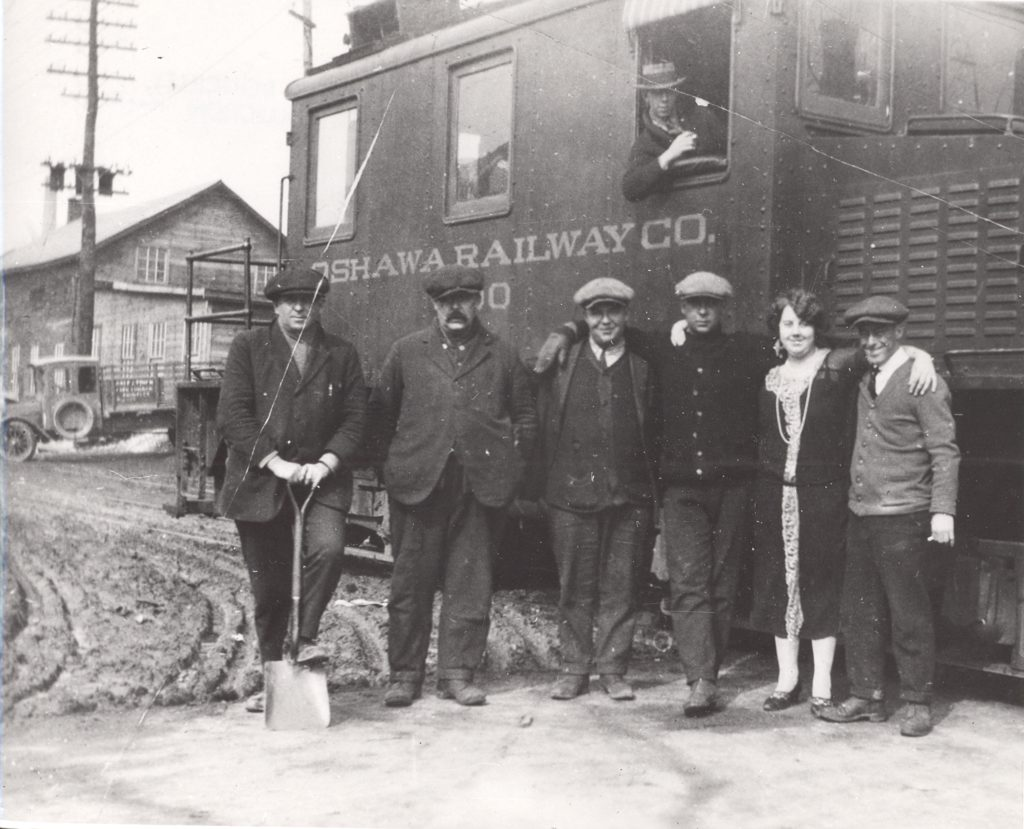 """Five men and one woman stand in front of a locomotive. The men are dressed in vests and ties, and the woman wears a dress that reached her ankles. The man to the far left has a shovel in his hands which he uses to perch up one foot. In the locomotive behind them, a man leans outside an open window. Along the locomotive reads, """"Oshawa Railway Co."""". In the background, a truck is parked in front of a wooden house."""
