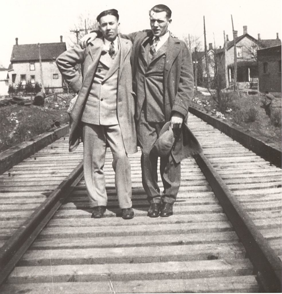 Two young men pose in the middle of train tracks. They are dressed in suits and long coats and have arms across each other's shoulders. Behind them are a residential area, with houses lined up on either side of the men.