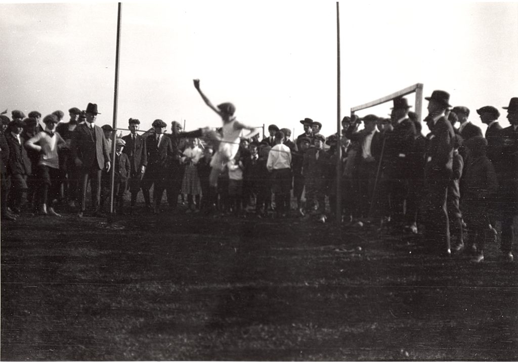 A group of people form a semi circle around the high jump pole. The high jump pole is made of two posts about eight feet apart and a pole running between the two. The group is mostly made up of men, adolescent to young adult, dressed in suits, coats and hats. The student jumping the pole is a adolescent boy, dressed in a tank top and shorts. He is a blur as he jumps the pole with his left leg first.