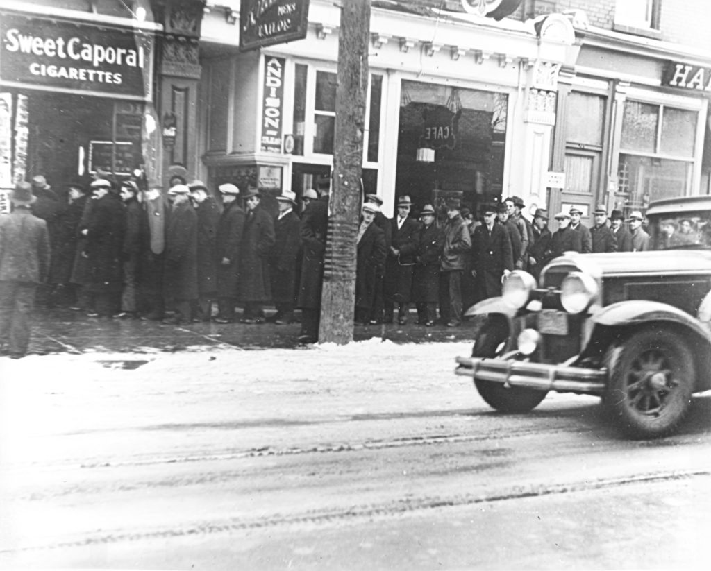 """A thick line of men assemble alongside the sidewalk. They are dressed in long coats and hats. The line ends at a building with a sigh that reads, """"Sweet Caporal Cigarettes"""". In the foreground, a thin layer of snow is on the road and a car enters the frame from the right."""
