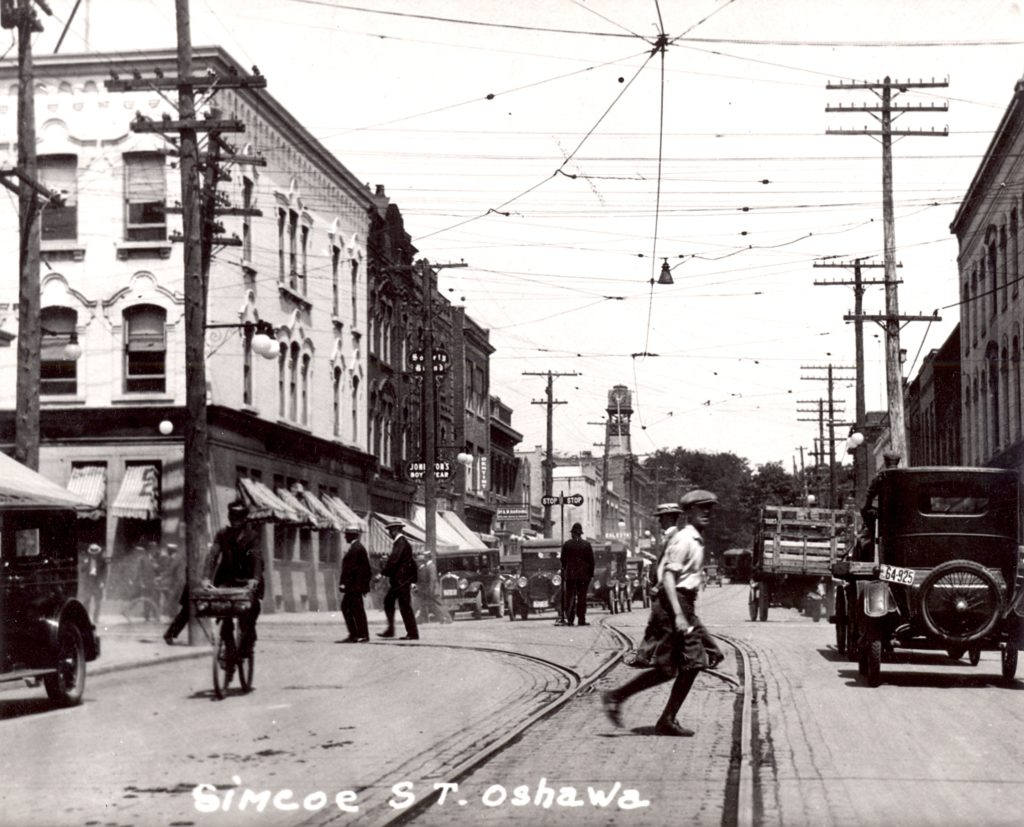 Set in a busy intersection, this photo appears to have been taken in the middle of the street. Cars, bicycles, and pedestrians seem to cross the streets at free will. Along the top of the intersection, electricity wires crisscross. In the middle ground, a police officer stands in the middle of the the cars. Along the left side of the images, building line the street.