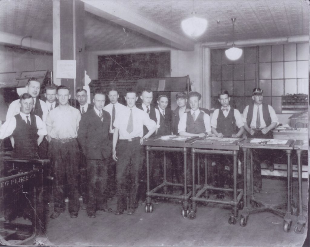 A group of young men, dressed in suits and varying vests and ties, line up and pose for the photo. In front of the group are three wheeled trays that appear to work spaces, completed with papers and pens or pencils.
