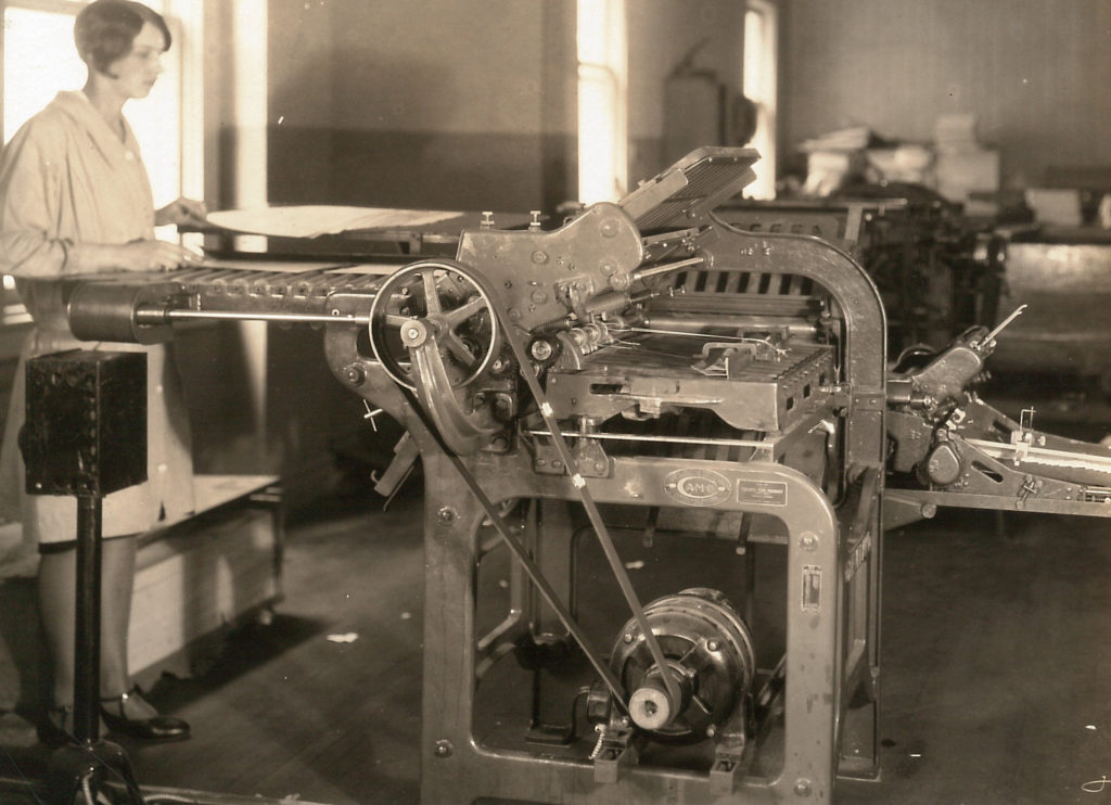"""A young woman operates a """"Cleveland Folder"""" machine. The machine is made up of pulleys, and wheeled trays that feed in paper. Newspaper sheets were fed into this machine, assembled and folded."""