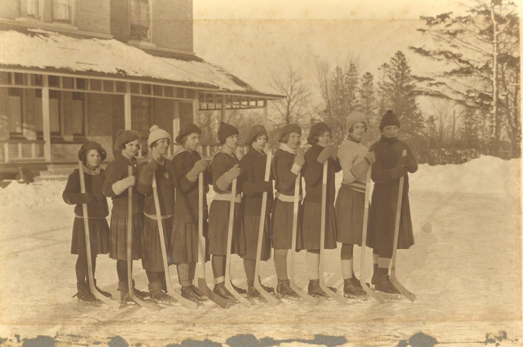 A lineup of young women dressed in winter clothes, and knee length skirts, stand on a homemade shoveled rink. They are all wearing skates and have a hockey stick in hand. Behind them is a wintry scene complete with house with snow on the roof and piles of snow.