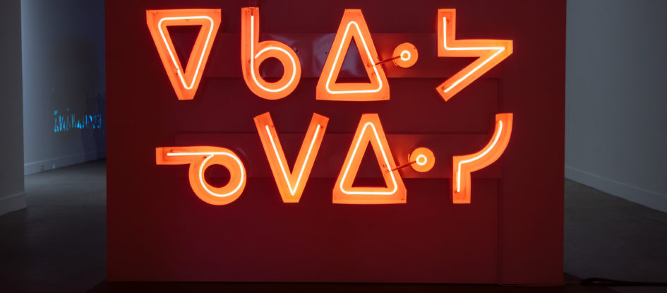 Orange neon channel sign hanging on a gallery wall that reads ekawiya nepewisi (don't be shy).